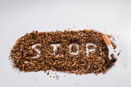 Creative background word stop written in tobacco on white background. The concept of smoking kills, nicatine poisons, cancer from smoking, stop smoking. Copy space.