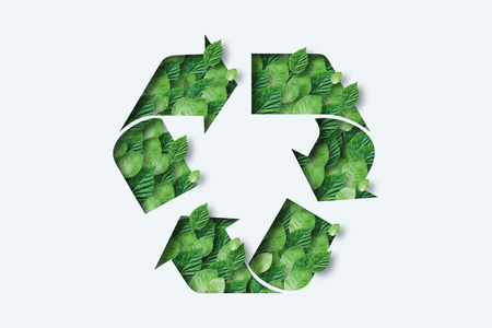 Recycling icon made from green leaves. Light background. The concept of recycling, non-waste production, eco-plastic, eco fuel.