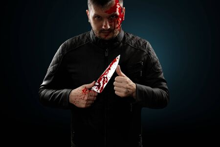 A serial killer, a maniac with a knife and splashes of blood. Halloween concept, psychopath. Copy space.