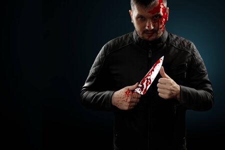 A serial killer, a maniac with a knife and splashes of blood. Halloween concept, psychopath. Copy space. Banque d'images