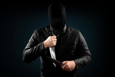 The serial killer, a maniac with a knife and a black chuolkom on his head. Halloween concept, psychopath. Copy space. Zdjęcie Seryjne