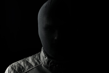 The serial killer, a maniac with a black chuolkom on his head. Halloween concept, psychopath. Copy space. Stock Photo