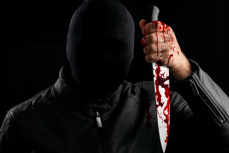 A serial killer, a maniac with a knife and splashes of blood. Halloween concept, psychopath. Copy space. Stock Photo