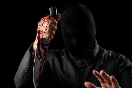 A serial killer, a maniac with a knife and splashes of blood. Halloween concept, psychopath. Copy space. Zdjęcie Seryjne