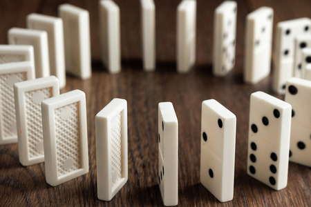 Creative background, white domino, on brown wooden background. Concept of domino effect, chain reaction, risk management, copy space. Stock Photo