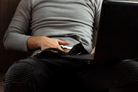 A man watches an adult video on a laptop while sitting on the couch. The concept of porn, masturbation, male needs, pervert, lust, desire, loneliness. Stock Photo