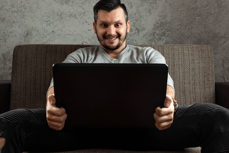 A man watches an adult video on a laptop while sitting on the couch. The concept of porn, men's needs, pervert, lust, desire, loneliness.