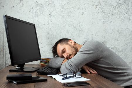 A man, a man sitting at a table in the office, and not working, tired look. The concept of office work, laziness, fatigue. Copy space.