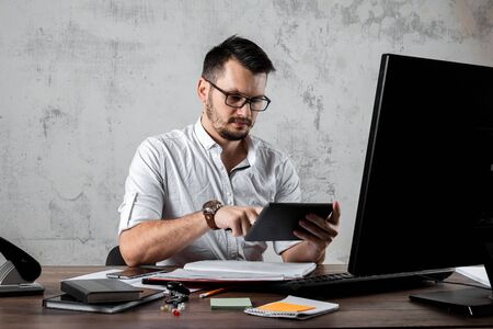 A man, a man sitting at a table in the office, playing in the phone. The concept of office work, laziness, fatigue. Copy space.