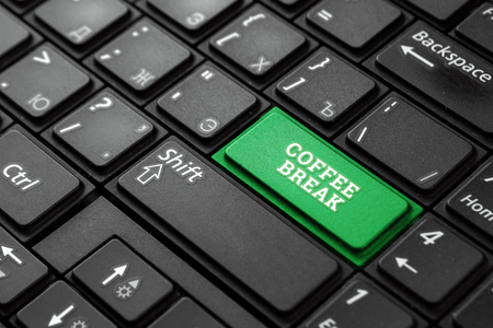 Close up green button with the word coffee break, on a black keyboard. Creative background, copy space. Concept magic button, break, lunch, rest.
