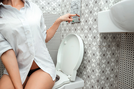 Close-up, a duck sitting on the toilet presses the flush button. The concept of intestinal problems, diarrhea, hygiene.