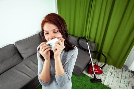 Beautiful girl with a napkin, sneezing from dust. A young woman looking desperately sick, breathing in the dust coming out of a vacuum cleaner. The concept is allergic to dust, laziness, cleaning.