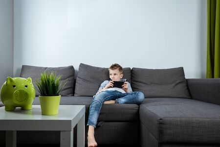 A boy sits on a sofa in the living room and plays with a smartphone. Boy texting on the phone. The concept of harming modern gadgets.