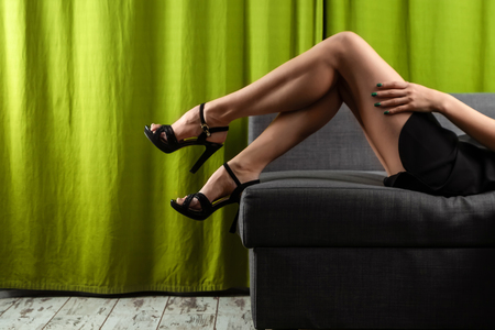 Female, beautiful, sexy legs in black branches, on a gray sofa. The concept of sex, relationships, adult sites, sexual desire.