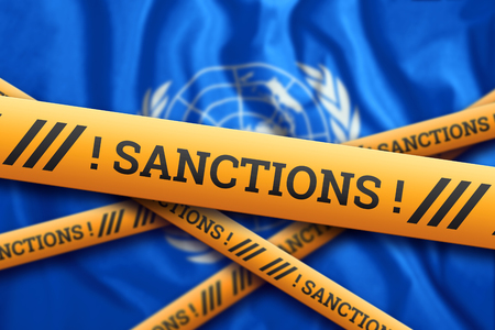 Creative background, inscription on UN flag, sanctions, yellow fencing tape. The concept of sanctions, policies, conditions, requirements, trade wars. 3d rendering, 3d illustration Фото со стока