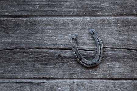 Vecchio ferro di cavallo su una vecchia tavola di legno. Il concetto di fortuna, fortuna, fortuna. Archivio Fotografico