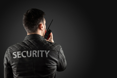 The man, security, is holding a walkie-talkie. The concept of protection, protection of information, bodyguard. Stock Photo