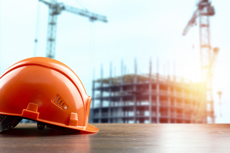 Orangeconstruction helmet close-up on the background of construction. The concept of architecture, construction, engineering, design. Copy space.