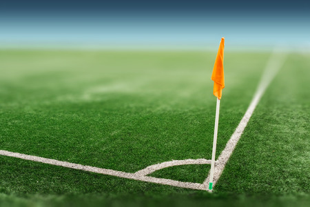 Green sports field with artificial grass. View from the corner of the orange flag on the football field. The layout of the football field in perspective.