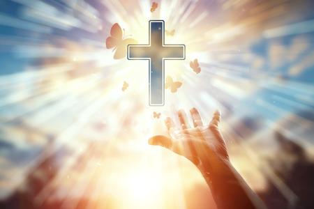 Close-up hand op de achtergrond van het symbool van christen, gebed, katholiek kruis, een zwerm vlinders vliegt. Christelijke religie, het concept van hoop, geloof, religie, een symbool van hoop en vrijheid.
