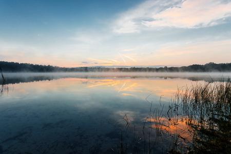 Mooie, rode dageraad op het meer. De stralen van de zon door de mist. De blauwe lucht boven het meer, de ochtend komt, het bos wordt weerspiegeld in het water. Stockfoto