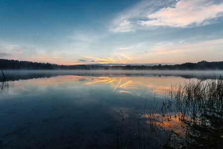 Beautiful, red dawn on the lake. The rays of the sun through the fog. The blue sky over the lake, the morning comes, the forest is reflected in the water. 写真素材