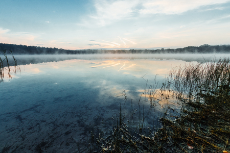 Beautiful, red dawn on the lake. The rays of the sun through the fog. The blue sky over the lake, the morning comes, the forest is reflected in the water. Stock fotó