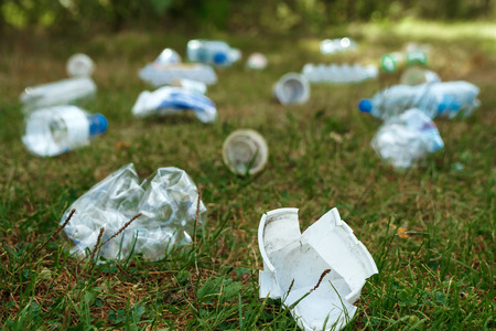 A pile of plastic on green grass, a problem in the natural environment, pollution of nature is not decomposing plastic. Protection of Nature. Stock Photo
