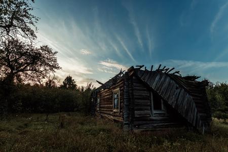 Sfondo creativo, una casa di legno abbandonata, una capanna contro un bel tramonto. Il concetto di sfondo magico, fantasia, misticismo, devastazione, vecchiaia. Archivio Fotografico