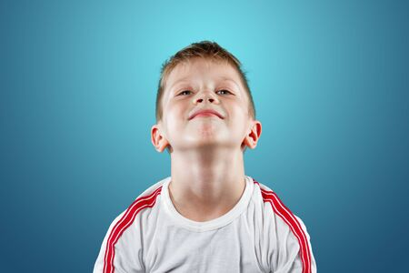 little boy with his hands up smiling on a blue background