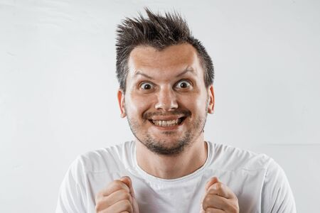 a man with a crazy look, a smile. The insane thoughts are crazy, obsessed with the idea. Stock Photo