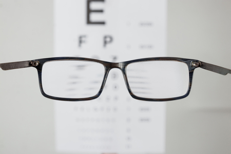 Close-up of eyeglasses for vision, pointing at table to check view. The concept of poor vision, blindness, vision testing, a trip to the ophthalmologist. Imagens