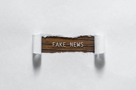 Fake News: un'iscrizione su un foglio bianco strappato. Il concetto di falsa informazione, manipolazione, propaganda.