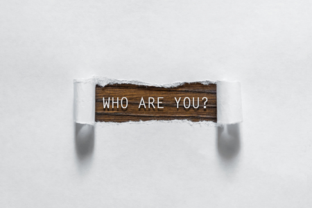 Who are you question written under torn paper. 写真素材