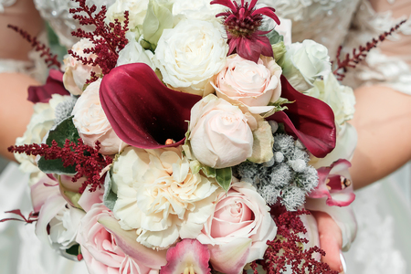 Beautiful bride is holding a wedding colorful bouquet. Beauty of colored flowers. Close-up bunch of florets. Bridal accessories. Female decoration for girl. Details for marriage 免版税图像