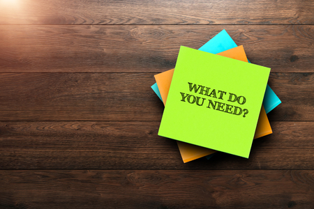 What Do You Need, the phrase is written on multi-colored stickers, on a brown wooden background. Business concept, strategy, plan, planning.