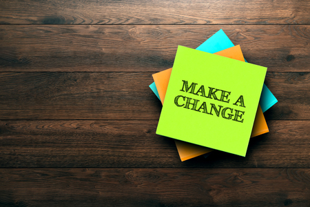 Make A Change, the phrase is written on multi-colored stickers, on a brown wooden background. Business concept, strategy, plan, planning.