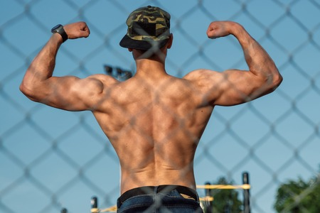 A young muscular guy with a torso resting after training, an athlete, outdoor training in the city