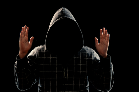 Silhouette of a man in a hood on a black background, the face is not visible, shows the palms in the camera. The concept of a criminal, incognito, mystery, secrecy, anonymity. Stock fotó
