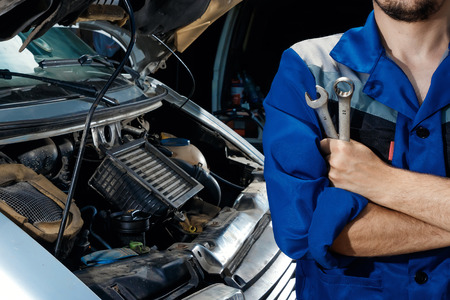 Male's hands close-up with wrenches. The auto mechanic works in the garage. Repair service. Maintenance of the car, car repair. Banco de Imagens