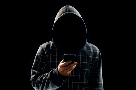 Silhouette of a man in a hood on a black background, his face is not visible, the hacker is holding the phone in his hands. The concept of a criminal, incognito, mystery, secrecy, anonymity.