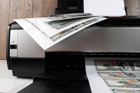 Impresora y dólares estadounidenses impresos, billetes falsos, falsificación de moneda. Falsificadores, imprenta, inflación. Foto de archivo