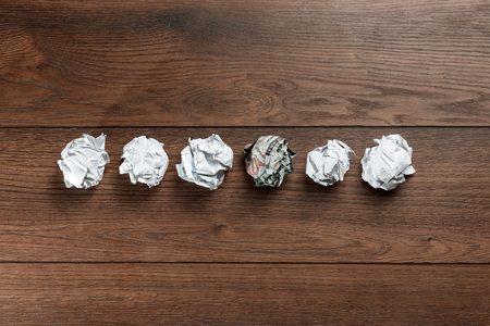 Crumpled paper on the table, one of them 100 US dollar bill. The concept is an alternative idea, a business idea, a creative idea. Difference, be different.