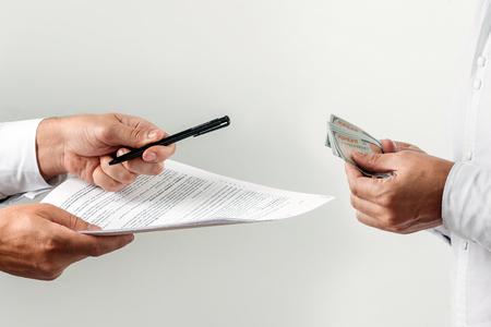 Hände, Geld, Angebote, einen Vertrag für ein Bestechungsgeld zu unterzeichnen, isoliert auf weißem Hintergrund. Hundert-Dollar-Scheine. Das Konzept gegen Korruption im Geschäftsverkehr, gegen Bestechung.