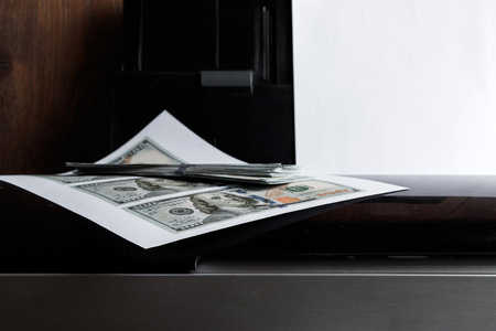 Printer and printed US dollars, counterfeit banknotes, currency counterfeiting. Counterfeiters, printing press, inflation.