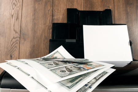 Impresora y dólares estadounidenses impresos, billetes falsos, falsificación de moneda. Falsificadores, imprenta, inflación.