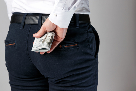 Money, dollars in your pants pocket. The concept of corruption, bankruptcy, collateral, crime, bribery, fraud, auction