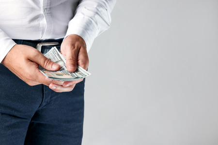 Male hands of businessman counting dollars close-up, light background.