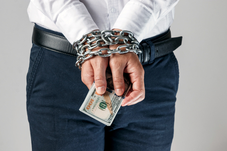 Hands of businessman with dollars prisoners in chains, handcuffs. The concept of combating corruption, bankruptcy, bail, crime, bribery, fraud, auction bidding Banco de Imagens