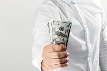 Geld in den Händen eines Geschäftsmannes, US-Dollar. Das Konzept von Korruption, Versprechen, Bestechung, Betrug, Auktionsgebote